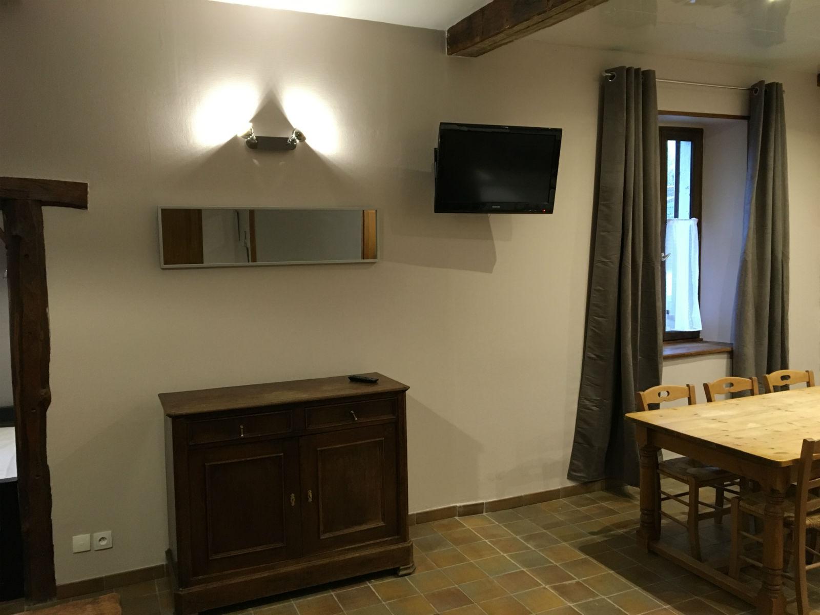 Pièce à vivre ouverte : espace salon avec TV écran plat.